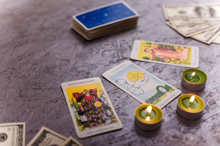Divination cards alignment with money and green candles. Mystery, astrology, fortune telling, belief and wealth concept.