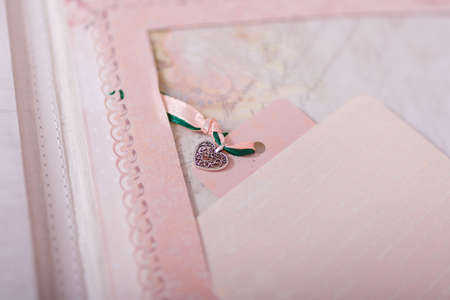 Soft focused close up shot of scrapbooking photo album page with paper decorative elements, metallic pendant heart, ribbons. Leisure and hobby concept.