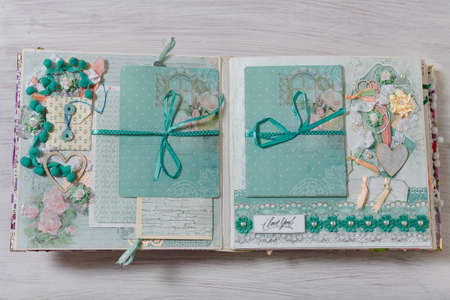 Scrapbooking wedding photoalbum spread with turquoise paper decorative elements, flowers, beads, tapes, ribbons, hearts and frames for phographs.