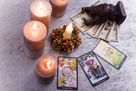 Divination cards alignment with black Buddha statue, money banknotes and candles. Mystery, astrology, fortune telling, belief, prosperity and wealth concept.