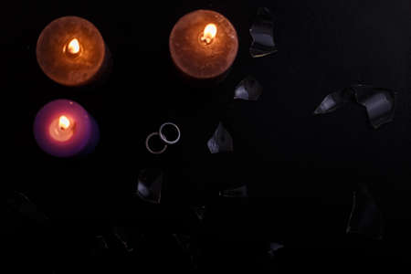 Love triangle and broken relationship concept. Wedding rings, broken glass and three burning candles on black background. Flat lay, top view, place for text.