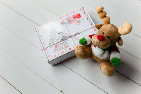 Wrapped Christmas gift and reindeer toy on white wooden table. Winter Holidays concept. Place for text. Stock Photo