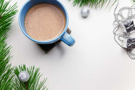 Blue cup of hot cacao or cappuccino with cinnamon standing on white table with pine branches and silver bulbs. Merry Christmas, Happy New Year and winter holidays concept. Copy space.
