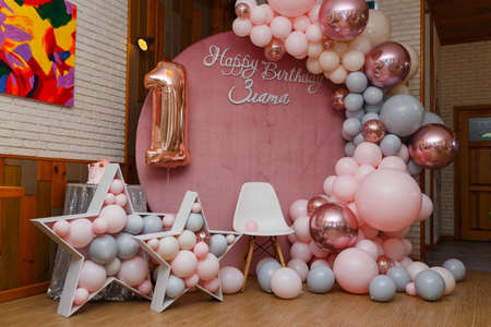 Beautiful festive decorations, pink and gray balloons arch, wooden stars, white chair and number one balloon on wooden round background. Little 1 year old girl birthday party photo zone.