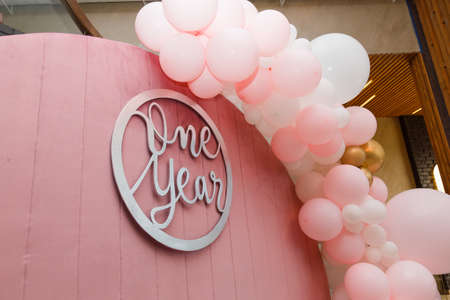 Beautiful festive decorations, pink and white balloons arch and number one on wooden round background. Little 1 year old girl birthday party photo zone.