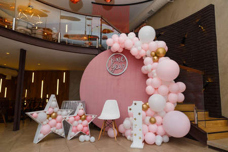Beautiful festive decorations, pink and golden balloons arch, wooden stars, white chair and number one on wooden round background. Little 1 year old girl birthday party photo zone.