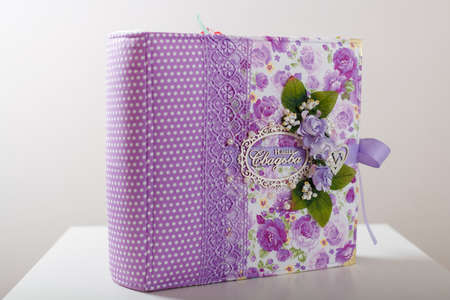 Fabric covered weddig scrapbook album with purple lace, flowers and inscription in Russian reads - Our Wedding.