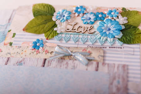 Soft focused close up shot of scrapbooking photo album page with paper decorative elements, flowers, lace, ribbons, beads, inscription Love. Leisure and hobby concept.