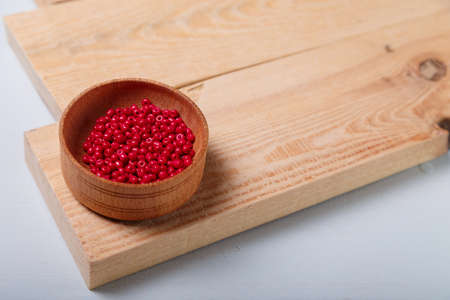 Close up of wooden bowl of red beads and buttons for sewing and embroidery. Set of materials for handcraft, making of bijouterie and accessories. Wooden background, copy space.