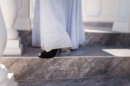 Beautiful female feet in high heeled shiny shoes with long tender white dress. School leaver or bride accessories and female clothing concept.