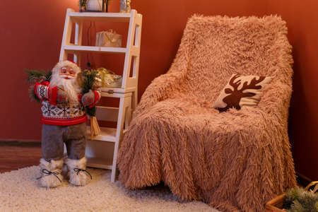 Santa Claus toy and arm-chair with brown plaid, pillow with reindeer pattern, white carpet. Merry Christmas time, New Year eve concept. Stock Photo