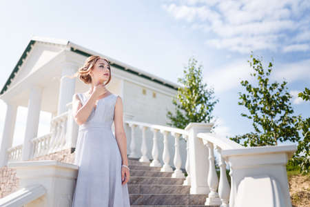 Beautiful girl in tender prom dress on stairs background. Female portrait on spring landscape. Banque d'images
