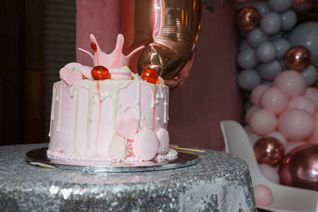Tender pink cake with hearts, macaroons and princess crown on shiny silver table cloth. Festive candy bar for 1 year old child. Little girl first birthday party.
