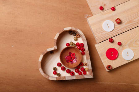 Close up of wooden heart shaped box of red beads and buttons for sewing and embroidery. Set of materials for handcraft, making of bijouterie and accessories. Wooden brown background, copy space.