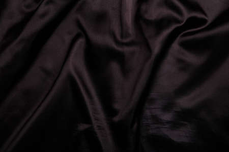 Suit or jacket lining, black shiny smooth wrinkled fabric texture, background or backdrop. Фото со стока