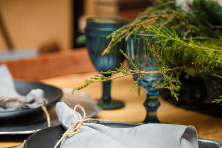 Soft focused shot of rustic style Christmas festive table, blue glasses, plates and fresh thuja branches bouquet. Eco-friendly green decorative elements.