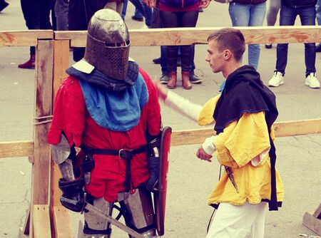 Knight Tournament in Dnipro city on 14.10.19, Ukraine. Historical fencing competition contest. assistant helps the contestant  before the fight 報道画像