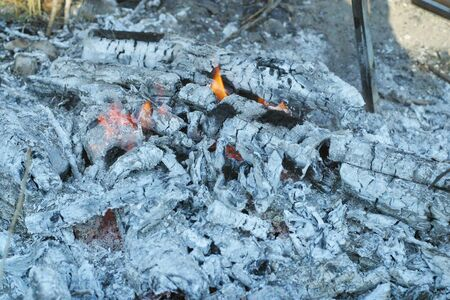 Ashes with some flames stayed after burning fire for preparing barbecue in hot summer day