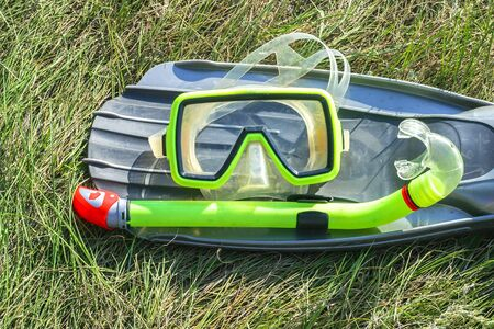 underwater mask, snorkel, and flippers lying on the grass. diver equipment