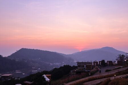 The sunset in a thai village near mountains in Chiang Mai, Thailand. The mountain scenery view 写真素材