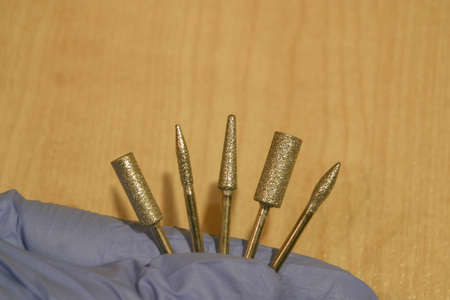 Set of milling cutters in a manicurist hand on wood background. Manicure and pedicure professional tools. Imagens