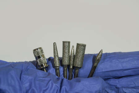 Set of milling cuttersi a manicurist hand. Manicure tool. Used manicurist professional tools in a hand on a white background.