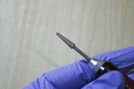 Milling cutter in a manicurist hand on a wood background. Manicure and pedicure professional tools. Stock fotó