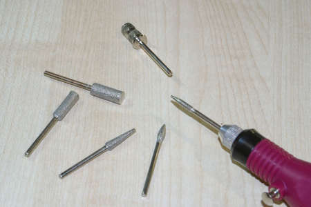 Set of milling cutters and milling machine on a wood background. Manicure and pedicure professional tools.