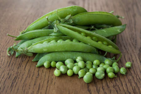 green been: Pods of green peas on a wooden background and pods of peas Stock Photo