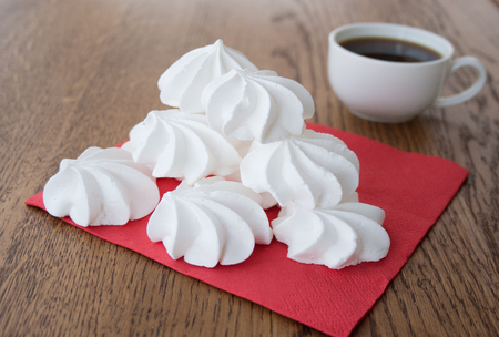 lite food: White meringue cake on a wooden background with a cup of coffee
