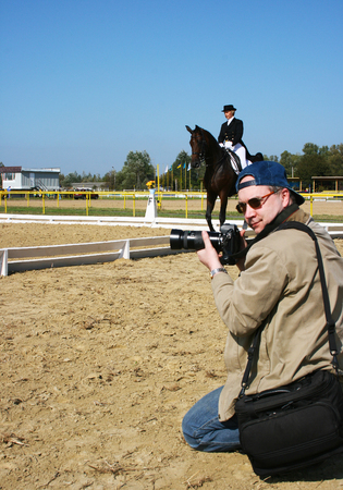 Kneeling Professional Press Photographer Who Turned His Head Our Way, Shoots Outdoor Equestrian Dressage Style Classic English Riding Sports Competition - Horsewoman Jokey on a Dark Brown Purebred Striding Horse in the Background Stock Photo