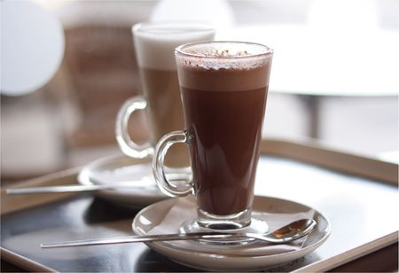 caffiene: Hot chocolate in a tall class with Cafe Latte on background