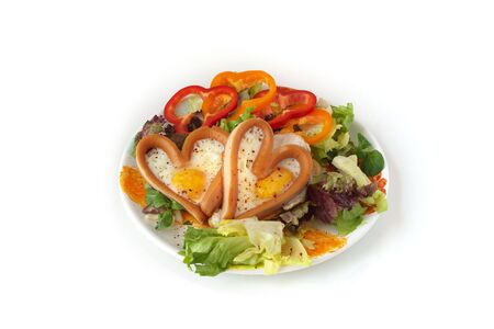 heart sausages with fried eggs on leafs salad for lovely breakfast  for Valentines day or weekend photo