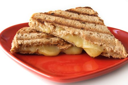 melted cheese: grilled traditional sandwich with melted cheese on red shape plate clouse-up Stock Photo