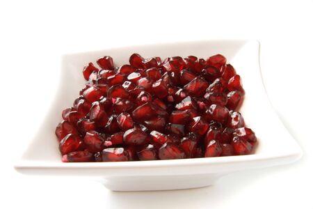 pommegranates: handfull of  pomegranate grains in white squared bowl