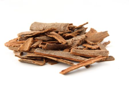 Cinnamon sticks chopped, isolated on white. Shallow depth of field, focused on the centre of the pile. photo
