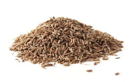 black seeds: whole cumin seeds, isolated on white. Shallow depth of field, focused on the centre of the pile. Stock Photo