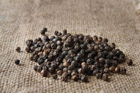 pile of black pepper on a burlap canvas photo