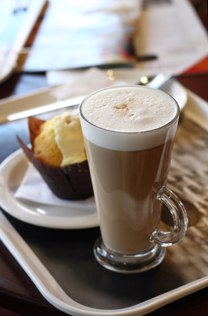 cappuchino: Cafe coffee - Latte in a glass with lemon muffin in background