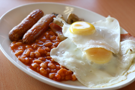 Traditional English breakfast - fried sausages, mushrooms, eggs and tomato baked beens