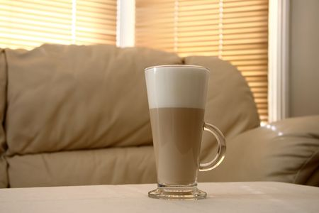 Cafe Latte in a tall glass and creamy sofa on background, soft focus Stock Photo - 1789626