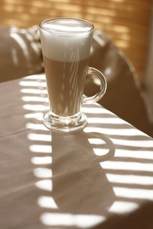 tall glass: Cafe Latte in a tall glass and long shadow Stock Photo