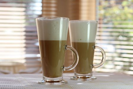 tall glass: Cafe Latte in a tall glass with another one and windows on background