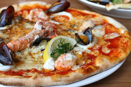 seafood pizza - lobster or langouste, mussels, prawns, squid rings, lemon and cheese. Stock Photo