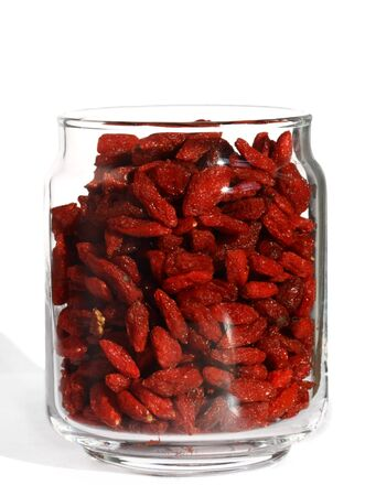 wolfberry: goji wolfberry in opened glass jar, bright color, white background and ligth shadow