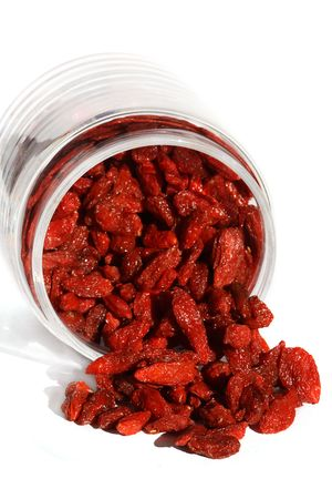 goji wolfberry with upset glass jar, bright color, white background and ligth shadow
