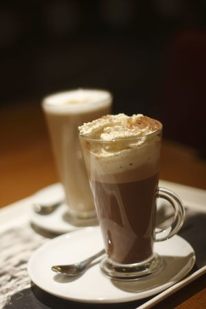 caffiene: Mint HOT CHOCOLATE with cream  in a glass and Coffee Latte in background, soft focus