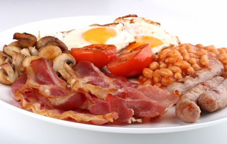english culture: Traditional English breakfast - tomatoes, fried sausages, bacon, mushrooms, eggs and tomato baked beens Stock Photo