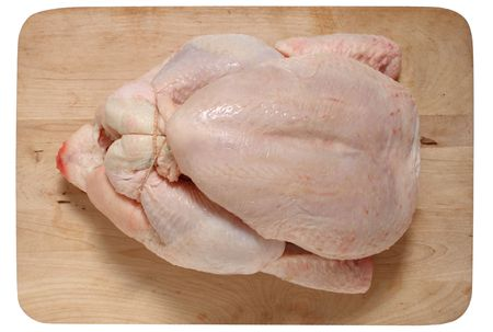 pullet: A whole chicken on a wooden board, ready for roast, isolated Stock Photo