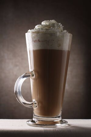 Coffee Latte in Tall Glass on brown rustic background